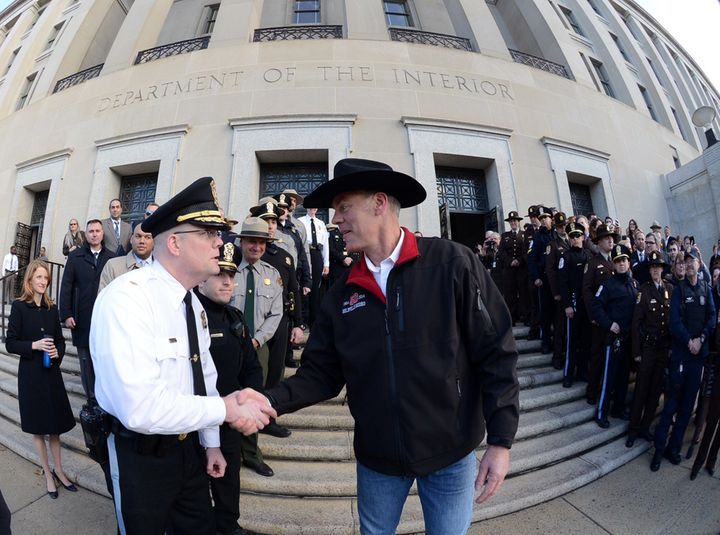 Interior Secretary Ryan Zinke, right, greets employees after riding in on horseback with a U.S. Park Police mounted unit to r