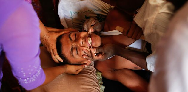 A 16-year-old with severe symptoms of rabies is comforted by family members in Myanmar, April 29,