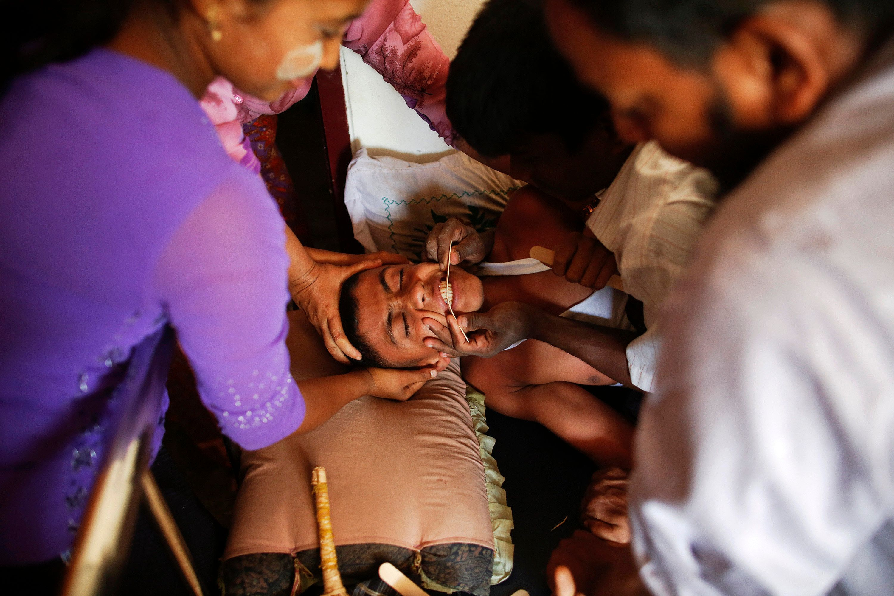 Wadulae, a 16-year-old Rohingya Muslim boy with severe symptoms of rabies, is comforted by family members at a local clinic at a camp for people displaced by violence near Sittwe April 29, 2013. Wadulae was bitten on the leg by a dog on April 6, and clinic officials say he has a slim chance of surviving. The boy failed to receive early treatment as none was available at the hospital. Myanmar authorities have begun segregating minority Muslims from the Buddhist majority in troubled areas of a country in transition. Picture taken April 29, 2013. To match Special Report MYANMAR-ROHINGYA/ REUTERS/Damir Sagolj (MYANMAR - Tags: POLITICS HEALTH RELIGION TPX IMAGES OF THE DAY CONFLICT)