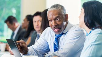 Senior adult African American man with gray hair and facial hair is pointing at a chart on a laptop computer. Man is sitting at long desk in business conference or seminar with mid adult Hispanic female professional colleague.