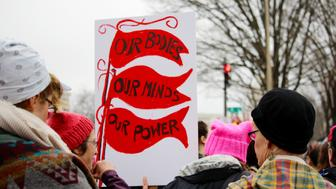 Crowds of women and men holding protest signs march through the streets during the Women's March on Washington, D.C.. Prominent sign says, 'Our Bodies, Our Minds, Our Power.' Protest. March. Community. Togetherness.
