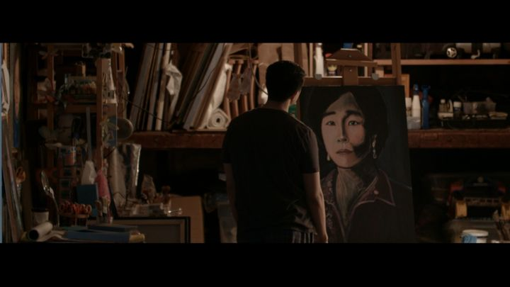 Thomas (Daniel Chan) looks at his long-abandoned painting of his mother in a scene from <strong><em>Song on Canvas</em></stro