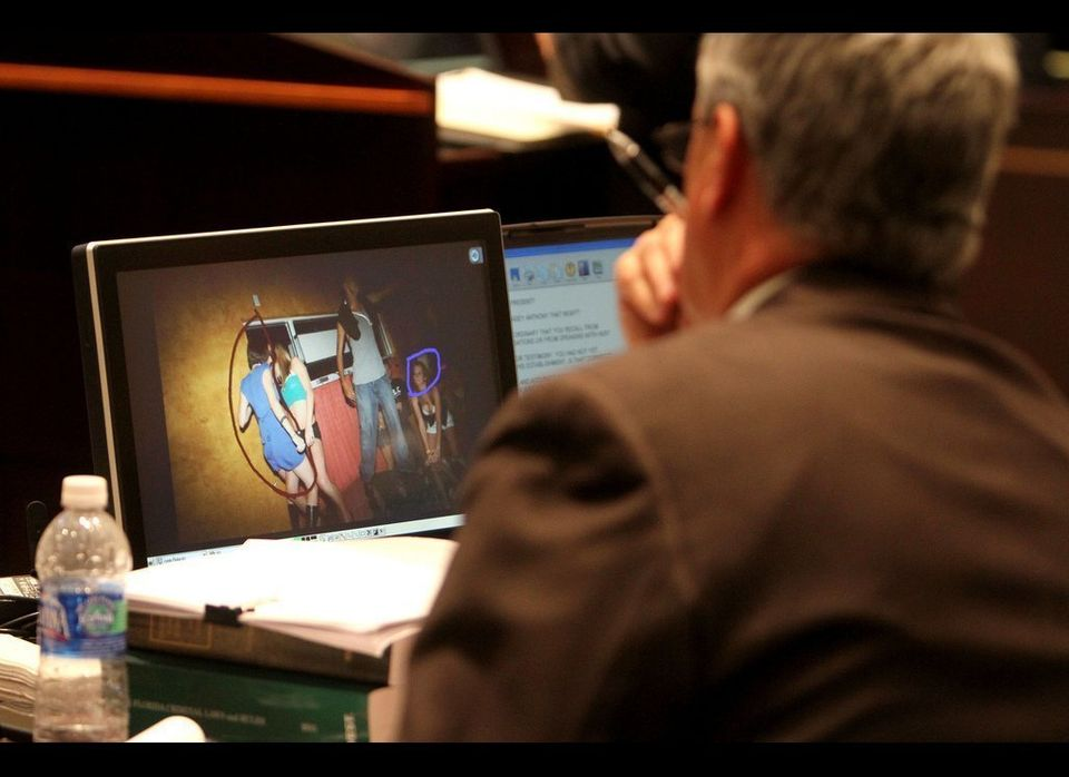 "Prosecutors look at a photo entered into evidence of Casey Anthony, in the the blue dress, dancing at a ""hot body"" contest in"