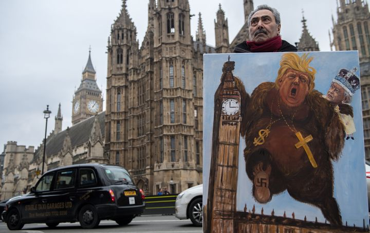 Artist Kaya Mar holds his latest political satire painting of Donald Trump depicted as King Kong with Queen Elizabeth II clim