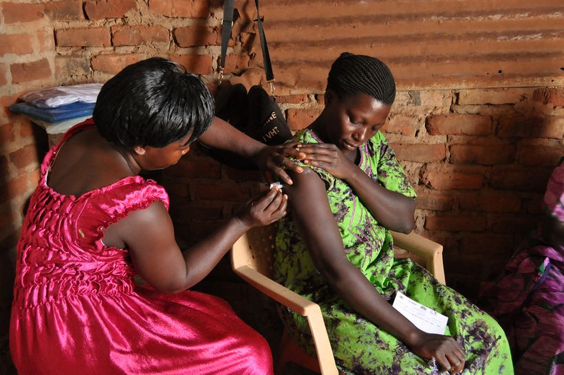 A community health worker with the Nawandala Village Health Team (VHT) gives the Sayana Press injection at her own home in Ki
