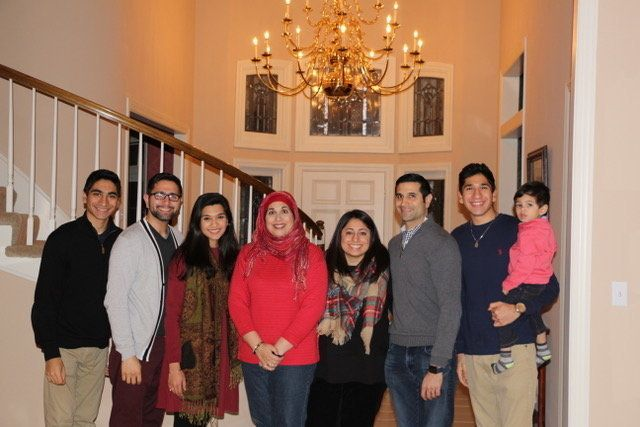 Mahnaz Shabbir with her four sons, two daughters-in-law and grandchild in her Kansas City home.