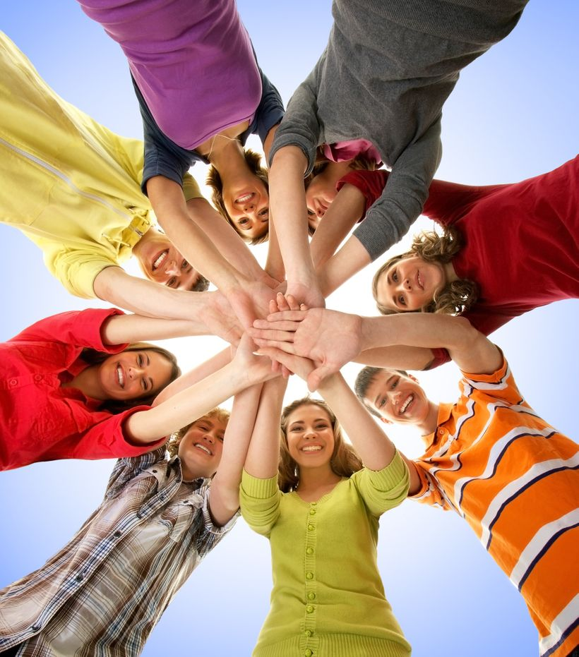 students in circle with hands together