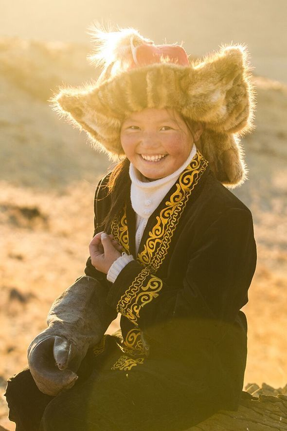 Aisholpan in traditional Mongolian dress with eagle hunt glove