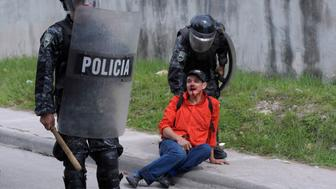 Riot policemen detain an injured peasant farmer as they evicted protesters near the Supreme Court in Tegucigalpa August 21, 2012. Riot policemen fired tear gas to remove peasant farmers who set up barricades and burned tires to block a main avenue as they demanded that a decree disallowing Bajo Aguan farmers in northern Honduras from being armed, be ruled unconstitutional by the Supreme Court. At least 20 farmers were detained after attacking policemen with rocks, reported local media. REUTERS/Jorge Cabrera (HONDURAS - Tags: CIVIL UNREST CRIME LAW)