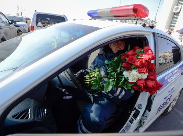 A traffic policeman gives flowers to female drivers ahead of International Women's Day.