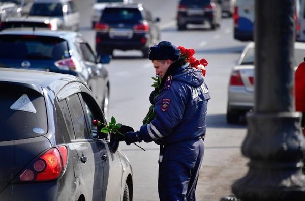A traffic policeman congratulates a female driver on upcoming International Women's Day in the citys Central Square.