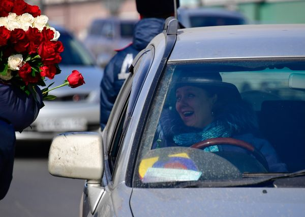 A traffic policeman congratulates a female driver on upcoming International Women's Day in the city's Central Square.
