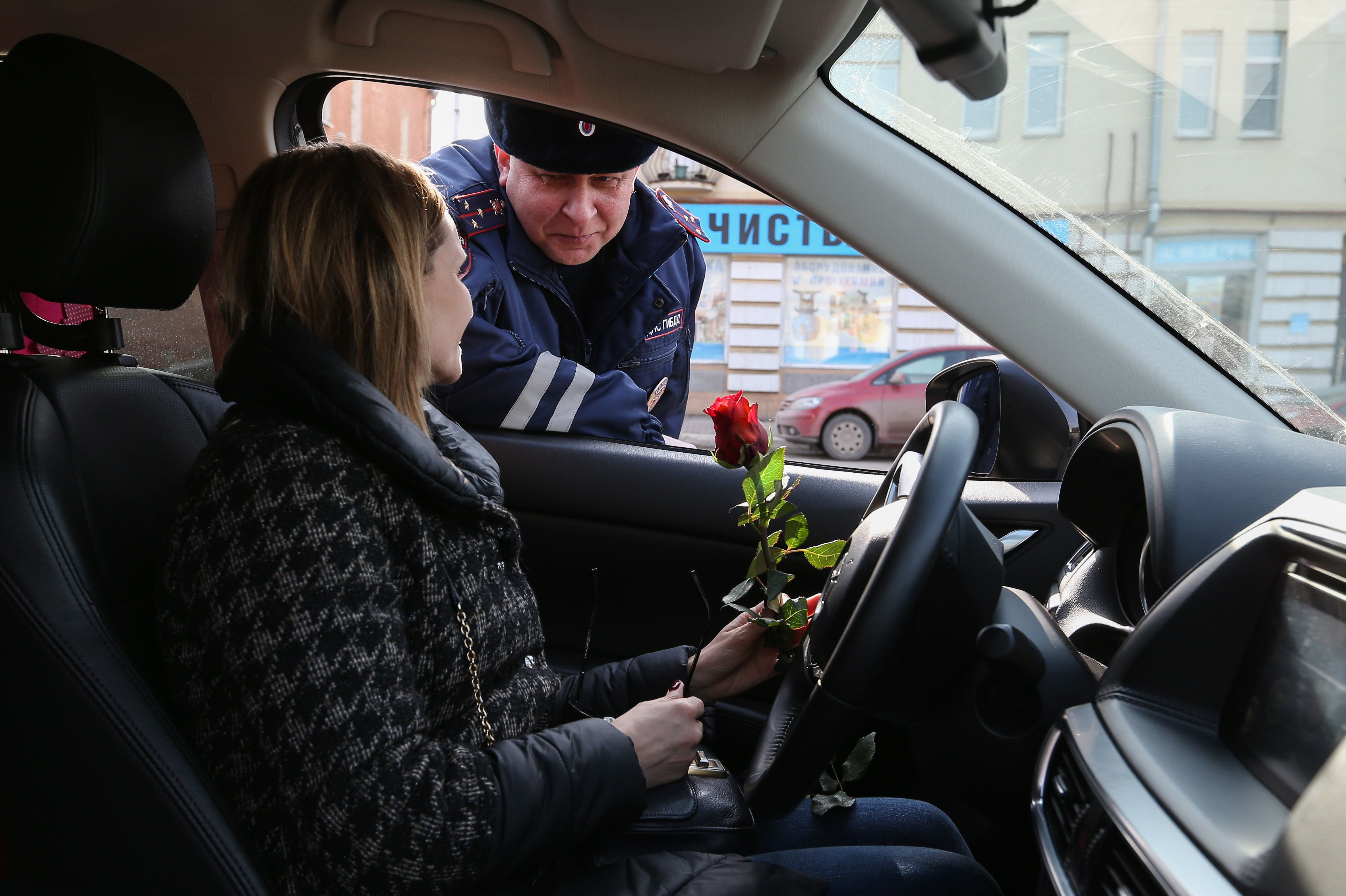 A traffic policeman congratulates a female driver on upcoming International Women's Day.