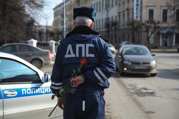 A traffic cop hides a rose before stopping a female