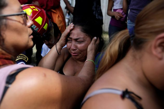 Family members react as they wait for news of their loved ones after a fire broke at the Virgen de Asuncion...