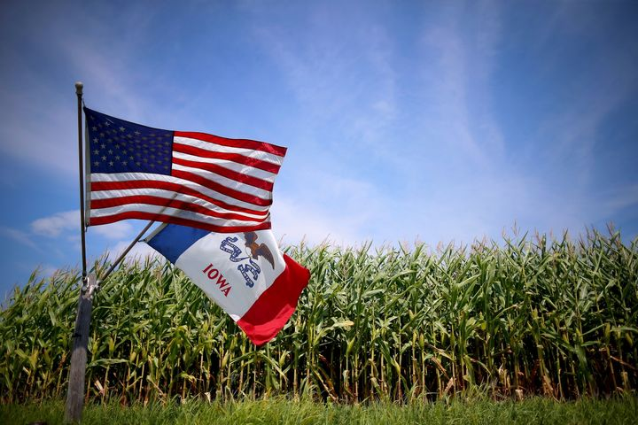 U.S. and Iowa state flags are seen next to a corn field in Iowa. The state has been the site of a long-standingbattle b
