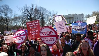 WASHINGTON, DC - MARCH 08:  Protesters hold signs as they march by the White House during a march and rally to support women's health programs and protest the White House global gag rule on March 8, 2017 in Washington, DC. Hundreds of women marked International Women's Day with a march and rally outside of the White House to protest the White House global gag rule and support women's health programs.  (Photo by Justin Sullivan/Getty Images)