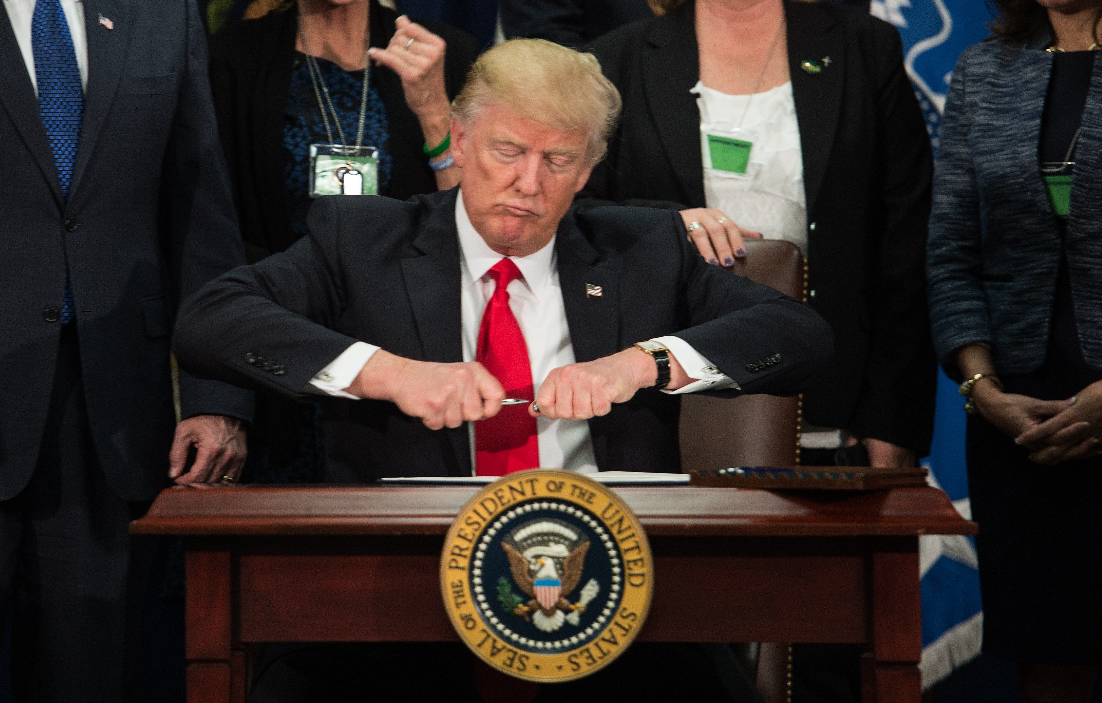 US President Donald Trump takes the cap off a pen to sign an executive order to start the Mexico border wall project at the Department of Homeland Security facility in Washington, DC, on January 25, 2017. / AFP / NICHOLAS KAMM        (Photo credit should read NICHOLAS KAMM/AFP/Getty Images)