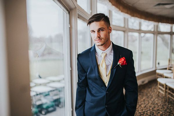 "Your handsome groom can channel the beast in a navy tux paired with a gold tie and vest. Complete the look with a single rose boutonniere. <i>Related: <a href=""http://www.bridalguide.com/dresses/complete-your-bridal-style/grooms-attire/stylish-groom-inspiration"" target=""_blank"" rel=""nofollow"">Beyond the Black Tux: Stylish Groom Inspiration</a></i>"
