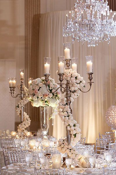 "Wrap your candelabras in roses for an even more romantic look. <i>Related: <a href=""http://www.bridalguide.com/planning/the-details/decor-flowers/lighting-ideas#154806"" target=""_blank"" rel=""nofollow"">25 Ways to Transform Your Wedding With Lighting</a></i>"