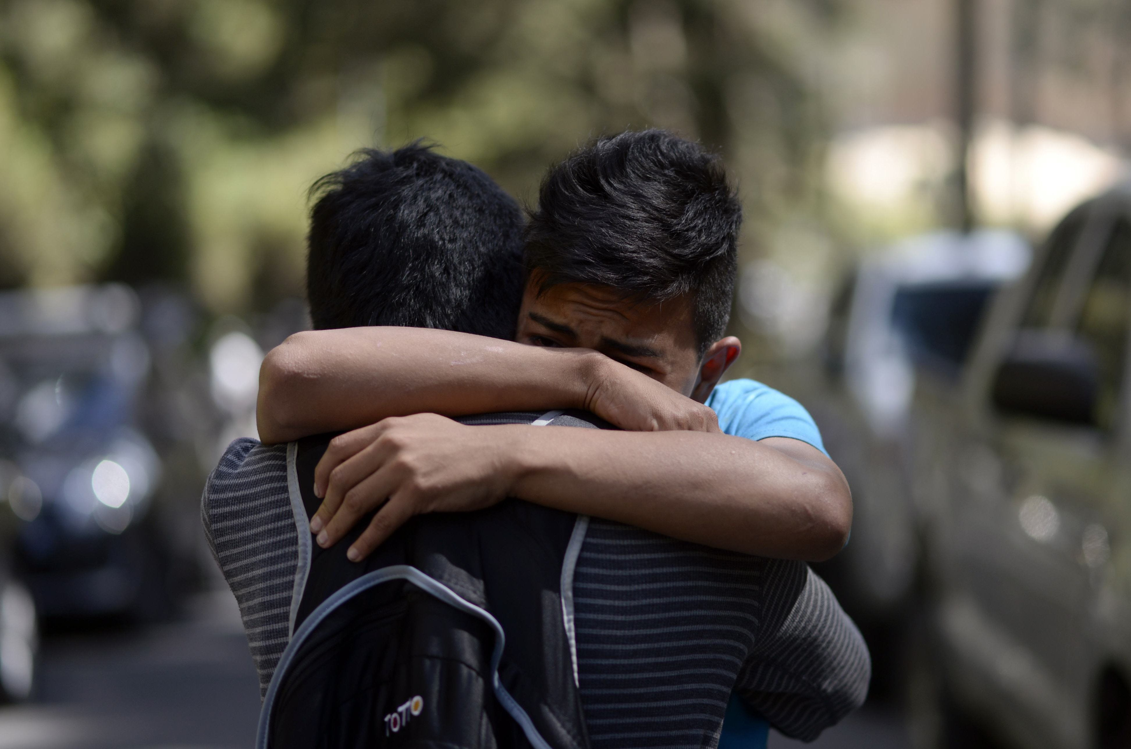A survivor of the fire (R) embraces a relative outside the children's shelter Virgen de la Asuncion after a fire at the facility killed at least 19 people, in San Jose Pinula, about 30 km east of Guatemala City, on March 8, 2017. At least 19 people died in a fire at a children's shelter in Guatemala, a spokesman for the local fire service said. It was not immediately known how many of the bodies were those of children. The center, supervised by state social welfare authorities, hosts minors who are victims of family mistreatment. The facility has been the target of multiple complaints alleging abuse, and several children have run away.  / AFP PHOTO / JOHAN ORDONEZ        (Photo credit should read JOHAN ORDONEZ/AFP/Getty Images)