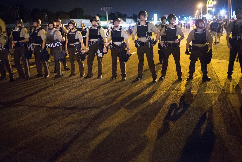 Police stand guard as demonstrators mark the first anniversary of the shooting of Michael Brown in Ferguson, Missouri, on Aug