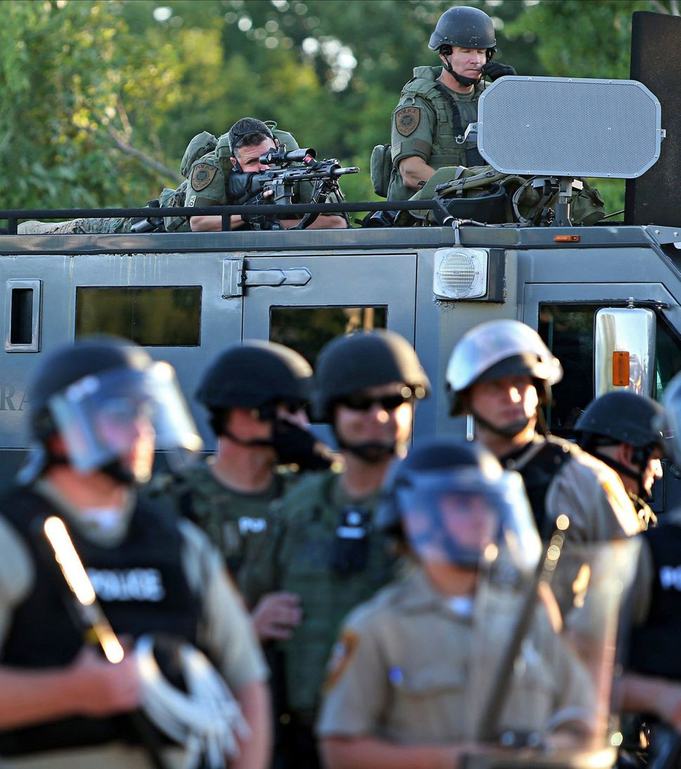 Police officers use military equipment on the streets of Ferguson, Missouri, days after the fatal shooting of Michael Brown.