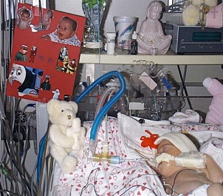 <em>Emma in the NICU, surrounded by photos of her big brother, Luke.</em>
