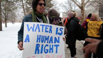 Demonstrators protest over the Flint, Michigan contaminated water crisis outside of the venue where the Democratic U.S. presidential candidates' debate was being held in Flint, Michigan, March 6, 2016. REUTERS/Rebecca Cook
