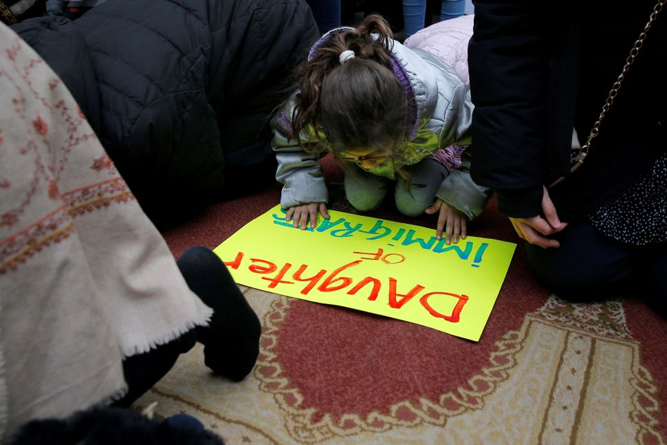 Eight year-old Esma, an Irish-Moroccan-American, prays with other Muslim women during a Boston protest against President