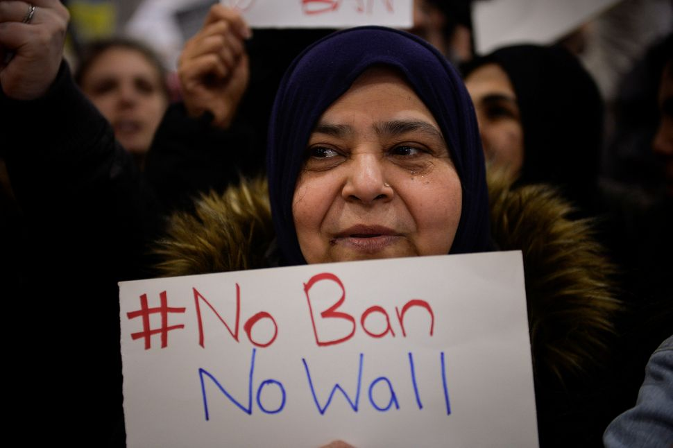 A Muslim women holds a sign during anti-travel ban protests outside Philadelphia International Airport in Philadelphia, Penns