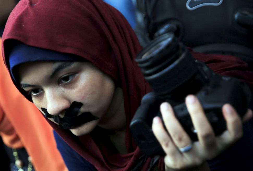 A news photographer with her mouth taped holds up her camera during a protest against the detention of Ahmed Ramadan, a photo