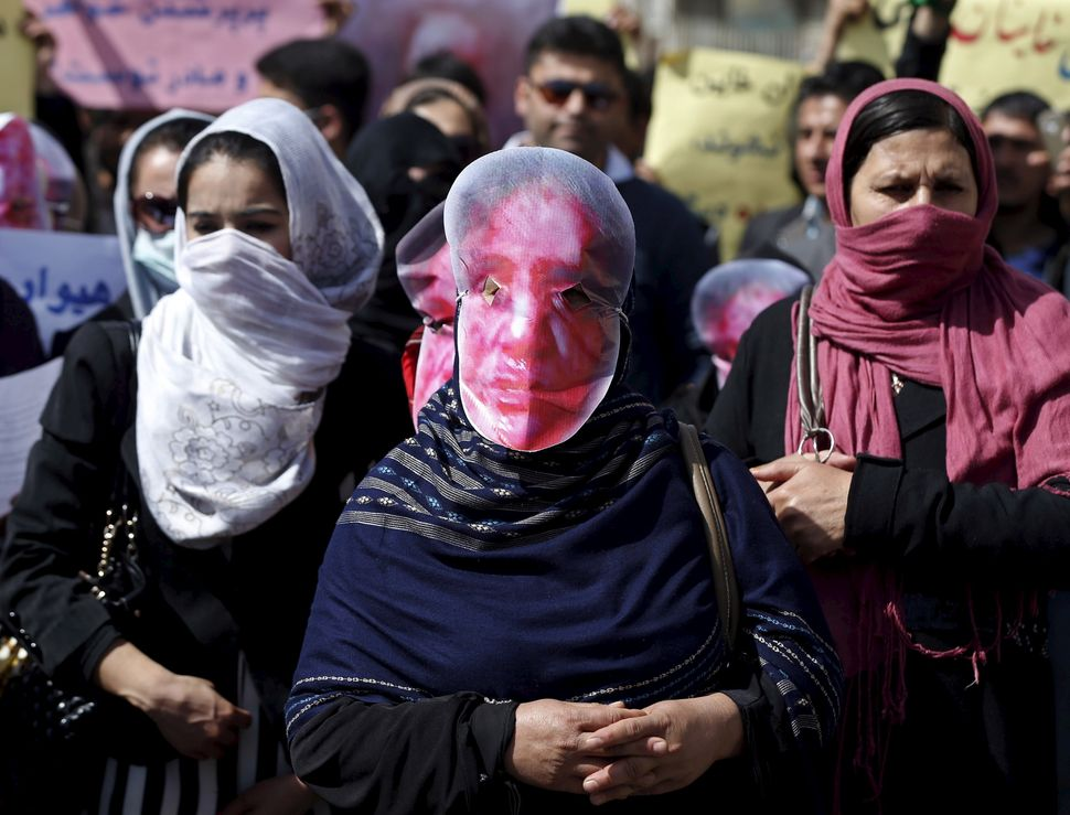 Afghans from the Hmbastagi party (Solidarity Party of Afghanistan) wear masks during a protest to condemn the killing of 27-y