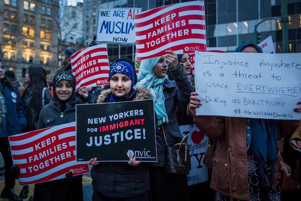 A Muslim girl holds a sign during the protest against Trump's executive orders, including the banning of Muslims fr
