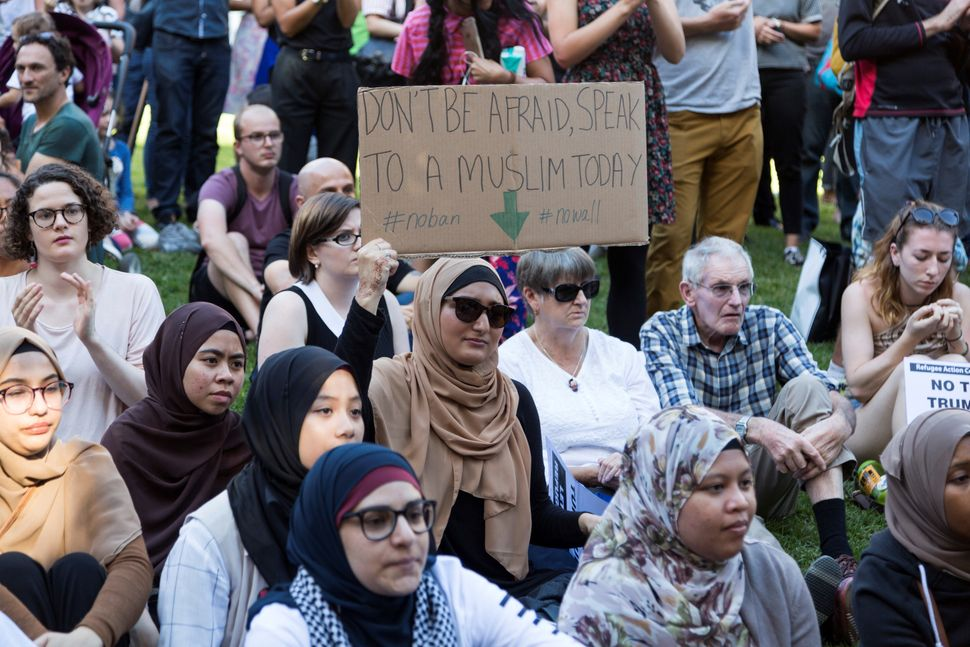 A Muslim woman holds a sign during a protest against President Donald Trump and his policies in Melbourne, Australia, Fe