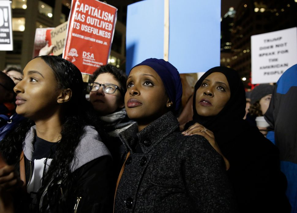 Ayla Ali (L-R), and her Somali refugee family members, cousin Ryan Adem and aunt Maryan Farah, listen to speakers at a rally