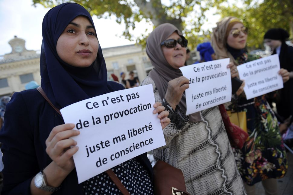 "Women hold signs reading, ""It is not a provocation, just my freedom of conscience"" during a headscarf march against Islamopho"