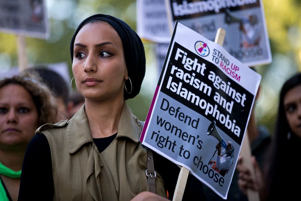 A woman joins a demonstration organized by 'Stand up to Racism' outside the French Embassy in London on Aug. 26, 2016, a