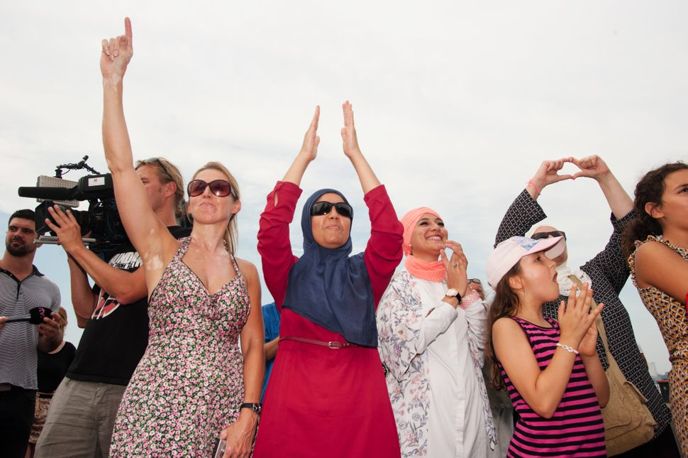 Women cheer in Antwerp at a beach party protest against the ban of burkinis in France.