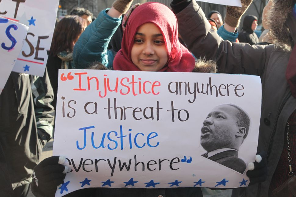 A Muslim girl holds a sign with a quote from Martin Luther King Jr. during a protest outside of the U.S. Consulate in downtow