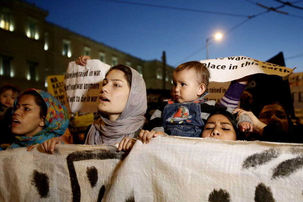 Migrant women from Syria and Afghanistan march outside the Parliament with their children. Around 2,000 refugees and migrants