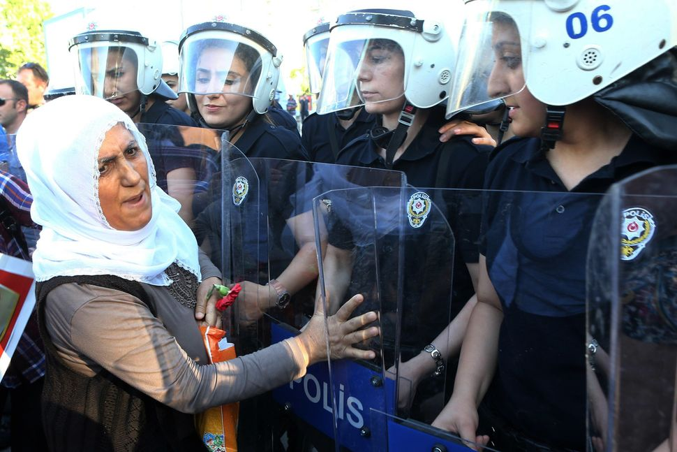 "Members of the Peace Mothers face police officers during a protest against a suicide bombing that killed <a href=""http:/"