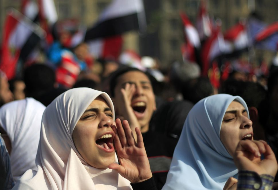 Egyptian Muslim women shout slogans as tens of thousands wave national flags during a rally on Jan. 25, 2012, in Cairo's Tahr