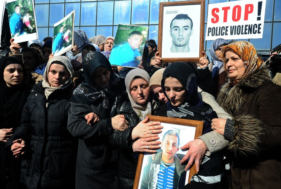 Women hold pictures of the two ethnic Albanian men killed by an off-duty ethnic Macedonian policeman, at a mass protest on th