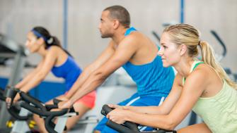 A multi-ethnic group of young adults are working out together while cycling in a spin class at the gym.