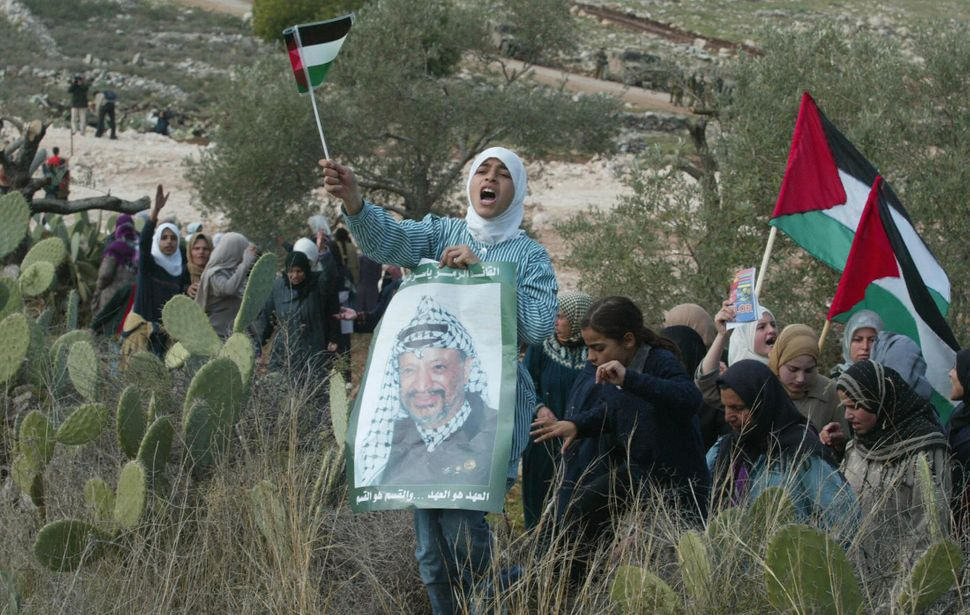 Muslim school girl holds a portrait of Palestinian leader Yasser Arafat and a national flag as she joins other women among hu