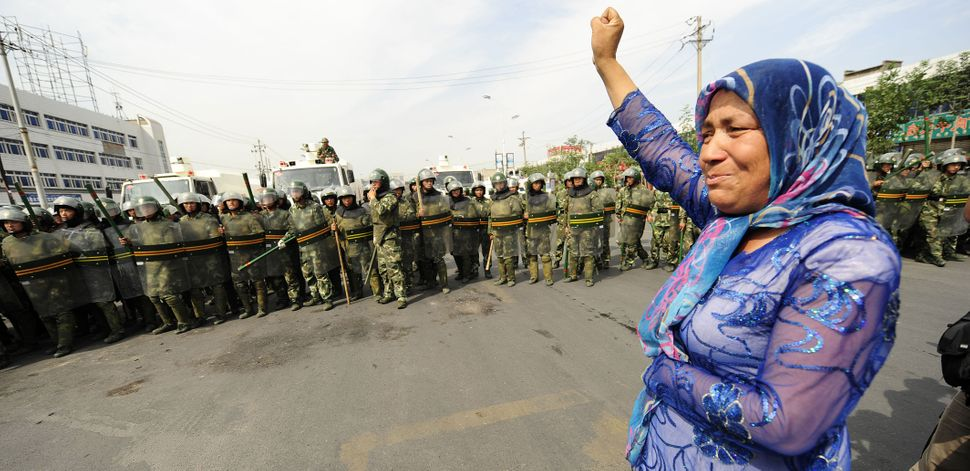 Chinese riot police watch a Muslim ethnic Uighur woman protest in Urumqi in China's far west Xinjiang province on July 7, 200
