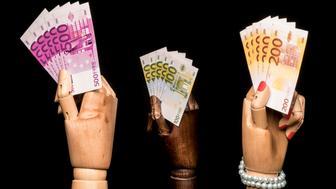A man's hand waving more money than a woman's hand ... but more than in the hand of a black. On black background.