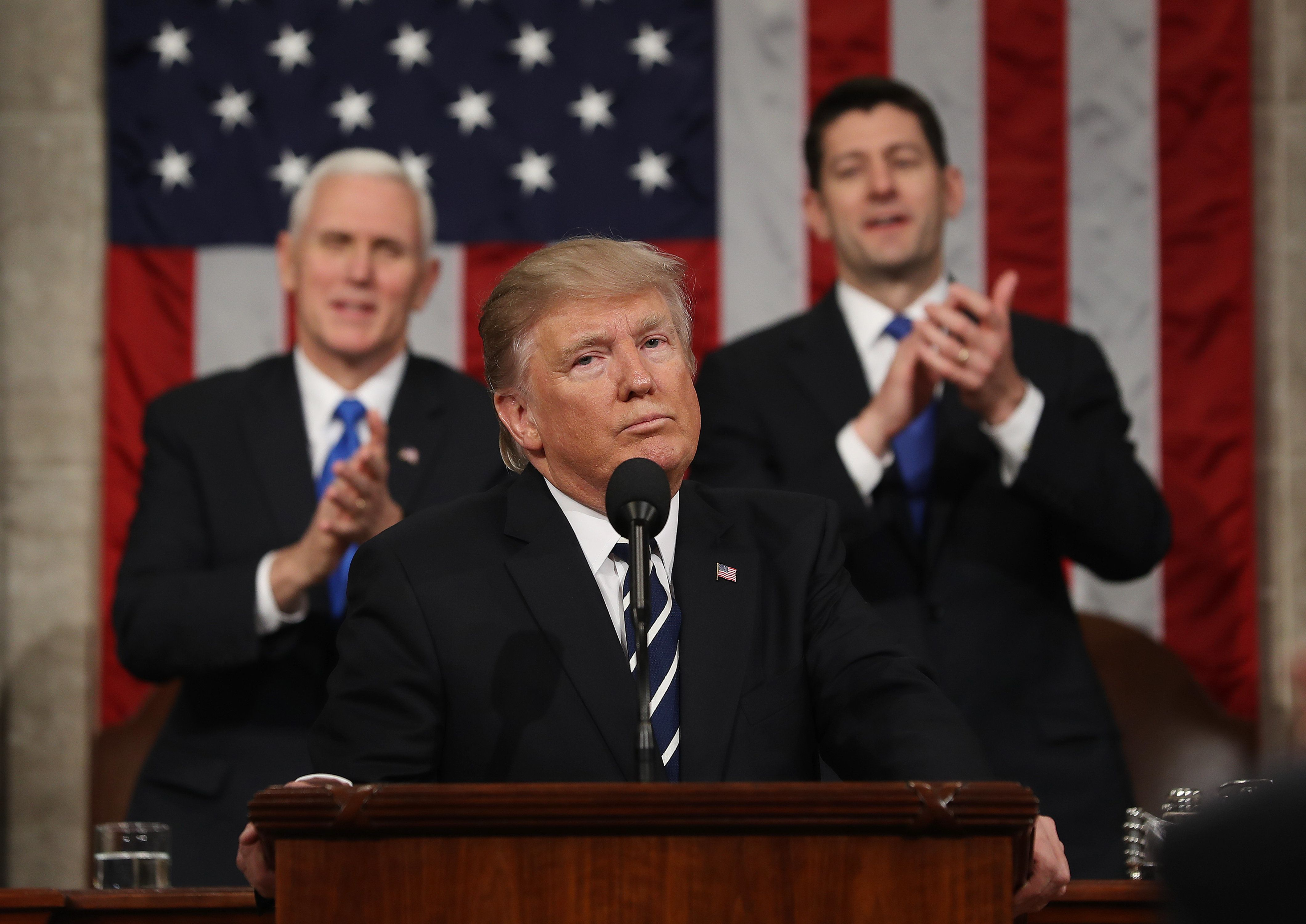 U.S. President Donald Trump, center, pauses as U.S. Vice President Mike Pence, left, and U.S. House Speaker Paul Ryan, a Republican from Wisconsin, applaud during a joint session of Congress in Washington, D.C., U.S., on Tuesday, Feb. 28, 2017. Trump will press Congress to carry out his priorities for replacing Obamacare, jump-starting the economy and bolstering the nation's defenses in an address eagerly awaited by lawmakers, investors and the public who want greater clarity on his policy agenda. Photographer: Jim Lo Scalzo/Pool via Bloomberg