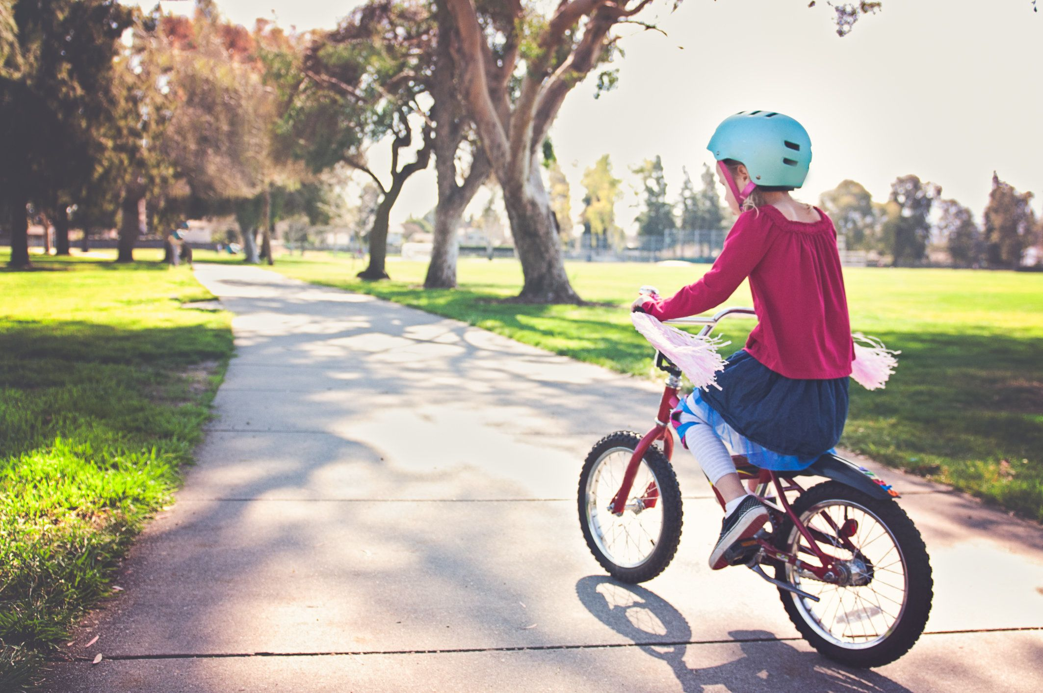A 5 year old girl is riding a bike on a path through a park.  There are trees and grass along the path.  She is wearing a light blue helmet and her bike has pink streamers that are blowing in the wind.
